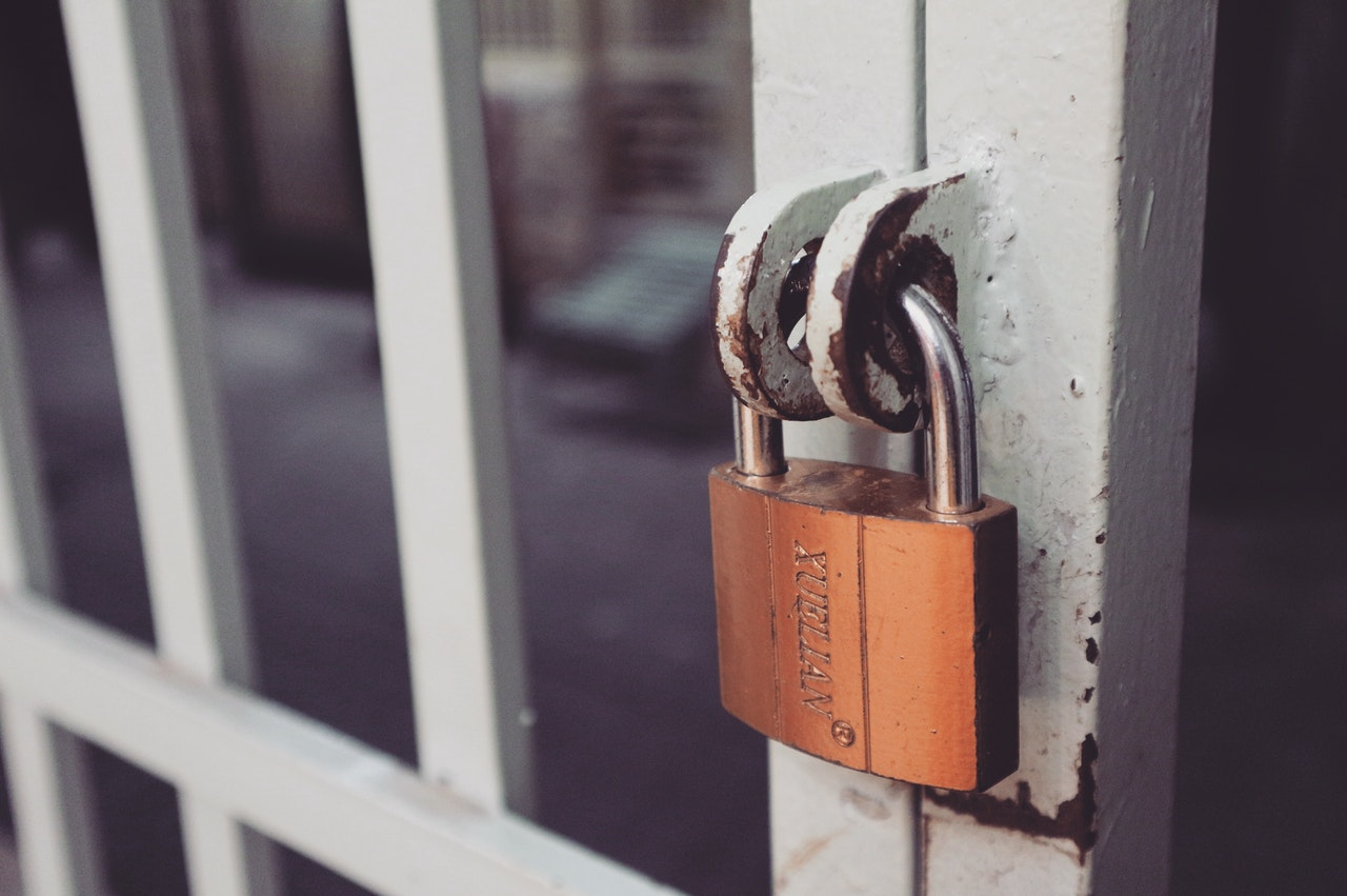 closeup photography of white gate with brass colored padlock 846288