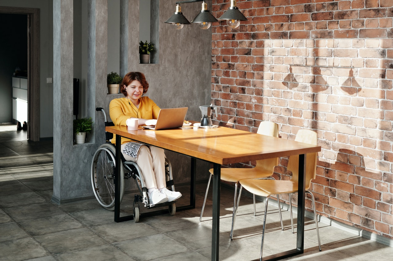 woman sitting on wheelchair while using laptop 4064700